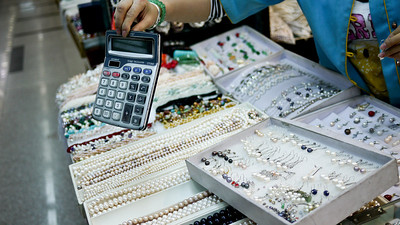 Vendor using the ubiquitous calculator to buy some pearls at the Pearl Market in Beijing, China.