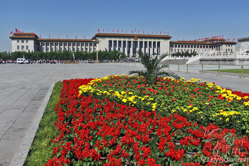China National People's Congress Building also known as the Great Hall of the People bordering Tian'anmen Square. Flowers in honor of China's Labor Day