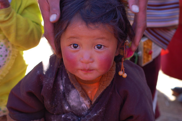 China, Sichuan, Litang: Little nomad girl shown off by her mother