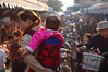 China, Sichuan, Leshan: Mommy and baby check out the market.