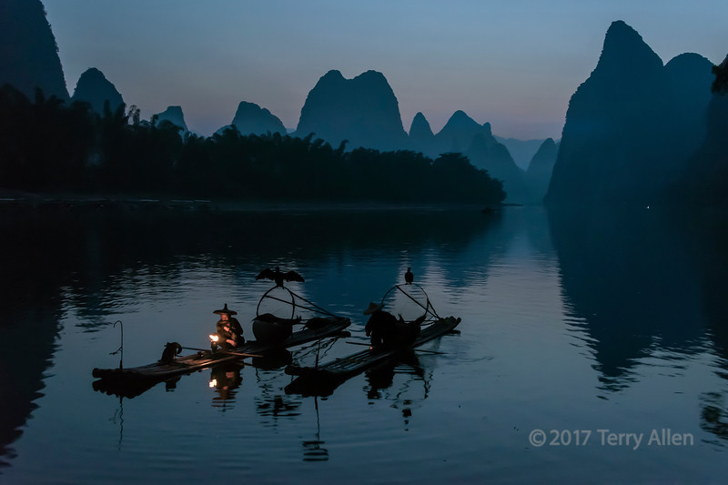 Pair of cormorant fishermen lighting their lanterns for early morning fishing, Li River, Xingping, Guilin, China