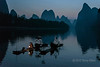 Pair of cormorant fishermen lighting their lanterns for early morning fishing, Li River, Xingping, Guilin, China