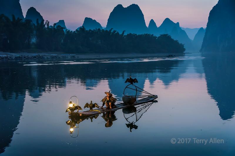 Cormorant fisherman taking early morning smoke break, Li River, Xingping, Guilin, China