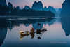 Cormorant fisherman taking early morning smoke break, Li River, Xingping, Guilin, China