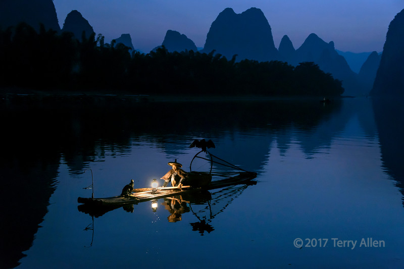 The cormorant fisherman have fished on the Li River near Xinping, Guilin, China for thousands of years. This fisherman, in traditional attire, is re-enacting the ancient practice of lighting his lantern on his bamboo raft in the pre-dawn and preparing to fish with his three birds. Pre-dawn the air pollution and mists are not as obvious as later in the day, so when these conditions prevail, pre-dawn is the best time to photograph the karst mountains.