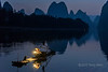 Cormorant fisherman preparing his lantern at dawn, Li River, Xingping, Guilin, China