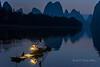 Cormorant fisherman preparing his lantern at dawn, Li River, Xingping, Guilin, China