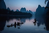 The cormorant fisherman on the Li River in Guilin Province, China prepare to fish with their trained birds in the quiet moments of the pre-dawn before they light their lanterns. Cormorant fishing has taken place in China for over 1000 years. The fishermen light a lantern at the bow of the boat to attract the fish and tie a line near the base of the bird's throat to prevent the birds from swallowing larger fish. When the birds are brought back aboard the bamboo rafts, the fish are retrieved.