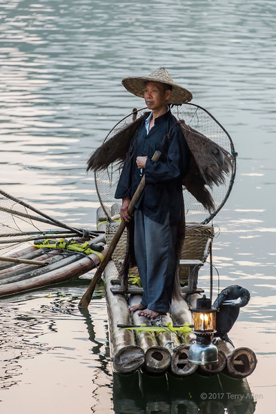 Portrait of a cormorant fisherman on his bamboo raft, Li River, Xingping, Guangxi Province, China