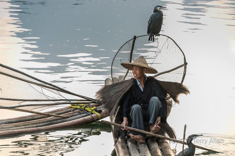 Portrait of a cormorant fisherman sitting on a bamboo raft, Li River, Xingping, Guangxi Province, China