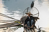 Portrait of a cormorant fisherman sitting on a bamboo raft, Li River, Xingping, Guangxi Province, China