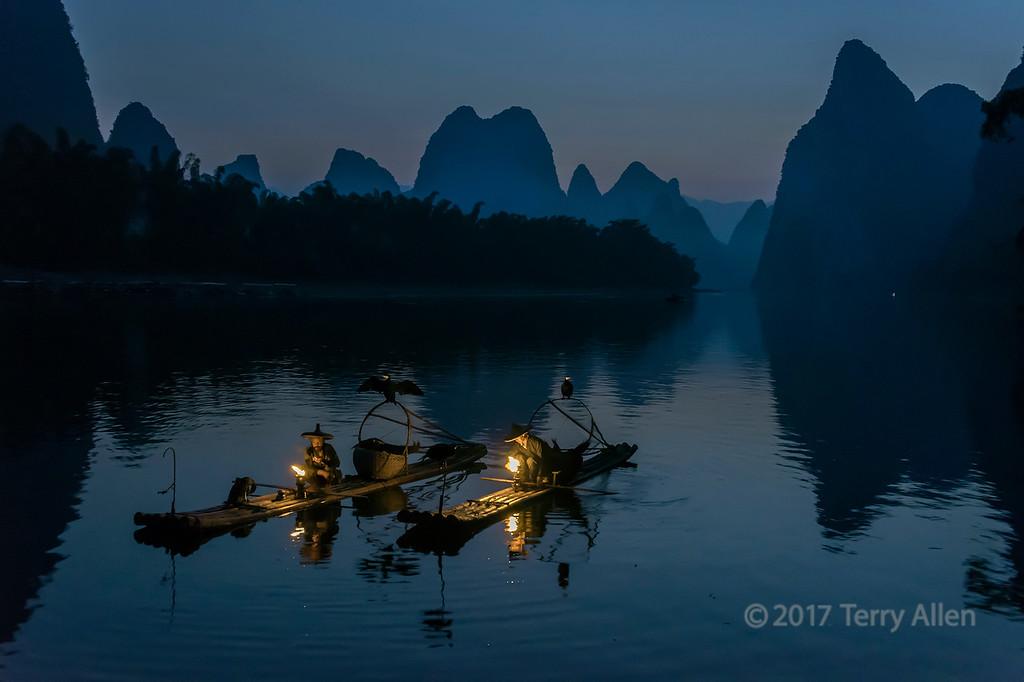 Pair of cormorant fishermen lighting their lanterns in the early morning, Li River, Xingping, Guilin, China
