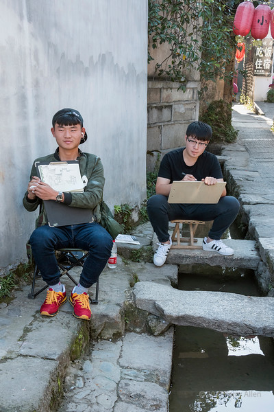 Young men drawing Hongcun Ancient Town by a small water canal, Lixian, Anhui, China