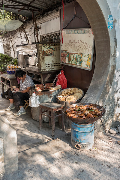 Vendor selling wok chicken and flat breads in a Moon Door, Hongcun Ancient Town, Lixian, Anhui, China