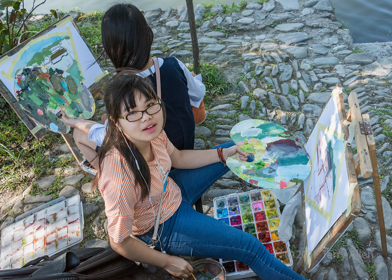 Young women painters on the shore of South Lake, Hongcun Ancient Town, Lixian, Anhui, China