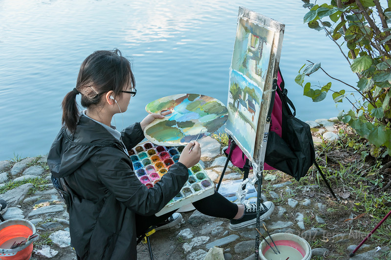 Artist painting a vieew of Hongcun Ancient Town from South Lake, Lixian, Anhui, China