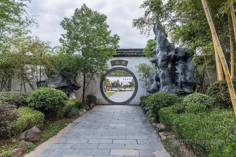 Moon gate looking through to bonsais ad miniascapes at Bao Family Garden, Shexian, China