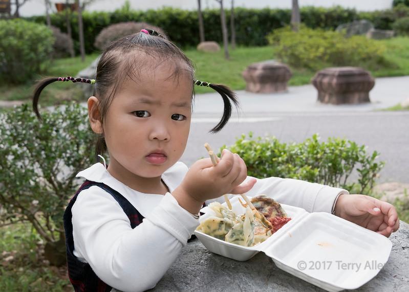 Wide-eyed young girl in cute pigtails with her lunch, Bao Family Garden, Tangyue, Shexian, Huangshan, Anhui, China