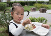 Wide-eyed young girl in cute pigtails with her lunch, Bao Family Garden, Tangyue, Shexian, Huangshan, Anhui, China