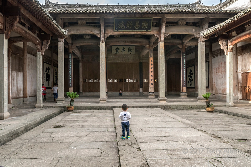 Small boy standing in Dun Ben Tang (Ancestral Hall for Men) Tangue, China