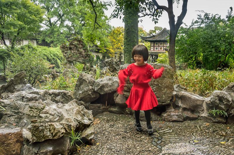 Small girl in red dress dancing in the rain, Liu Yuan Classical Garden, Souzhou, China