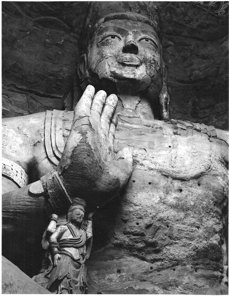 Large Buddha figure at the Yun Gang Grottoes near Datong. The smaller figure is commonly used to support the weight of Buddha's right hand. The figure is about 40' high.