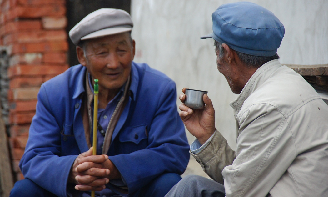 Today's daily travel photo is of two Chinese men sitting down and enjoying a candid conversation over a cup of tea in Dali, China.
