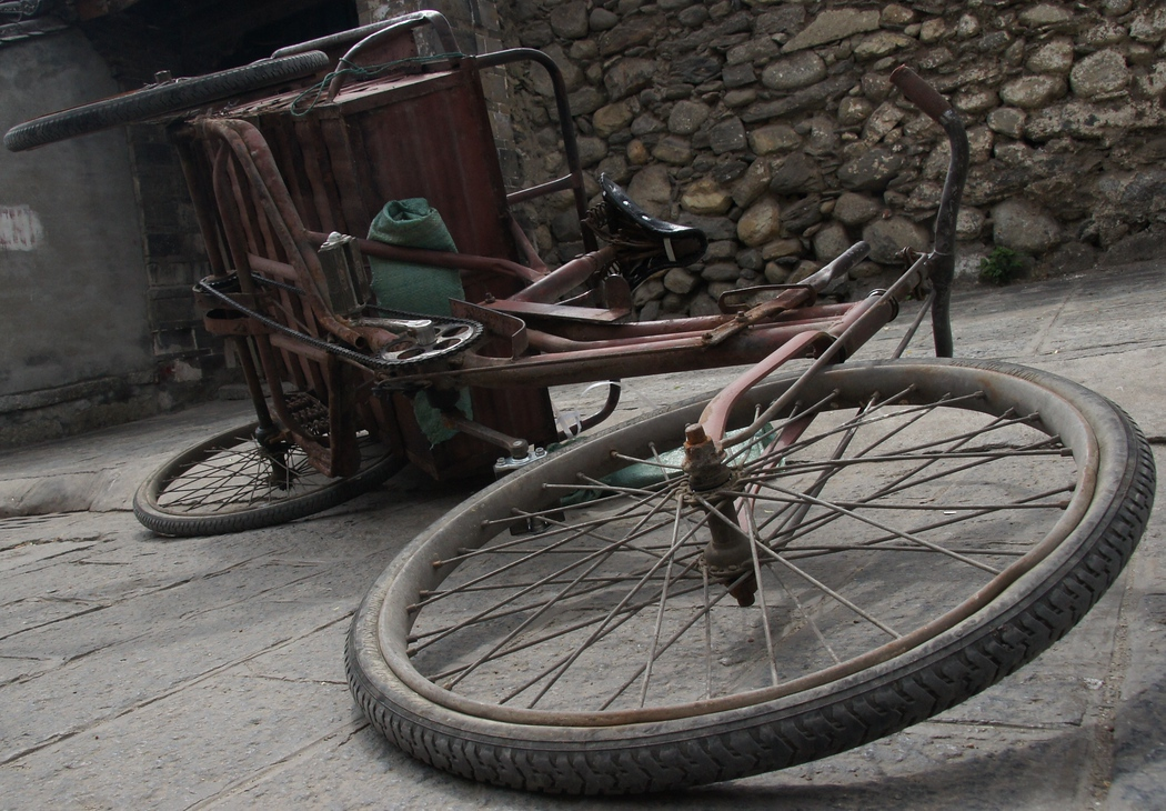 A turned over bicycle on the streets of Dali, China.  This is a travel photo from Dali, China.