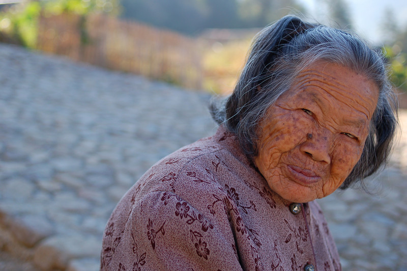 Old woman sits outside the Zhenchang Tulou
