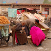 A Tibetan local and a monk make their morning bread purchases