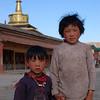 Pilgrim's children outside the kora prayer wheels