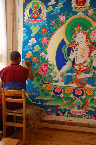 A senior monk working on a large thangka at the painting school