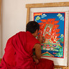 A monk working on his thangka at the painting school