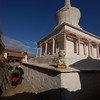 Pilgrims circle around a stupa on their kora