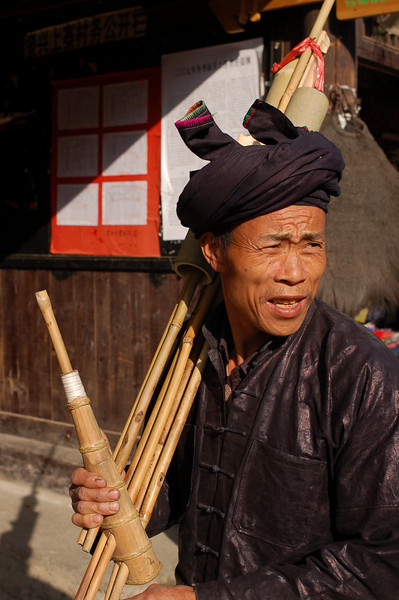 Dong man with a traditional bamboo instrument