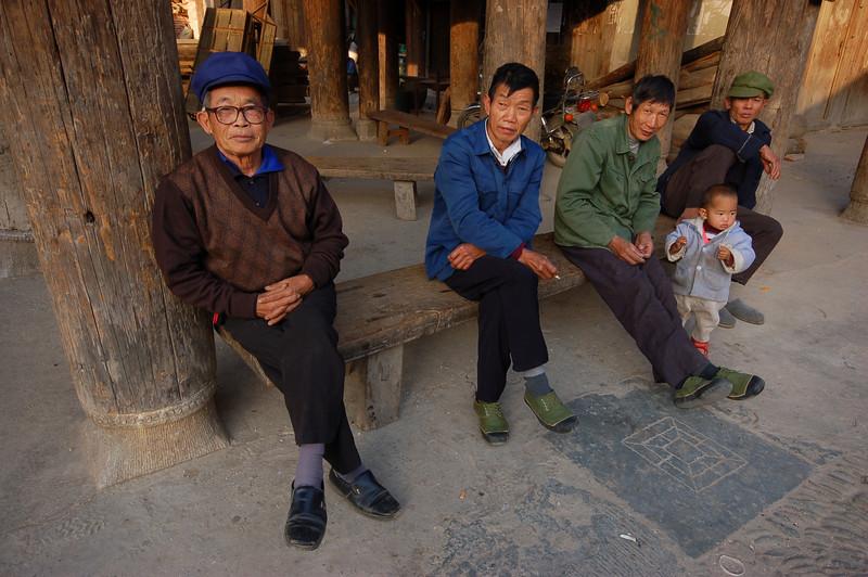 Local elders sit under the drum tower