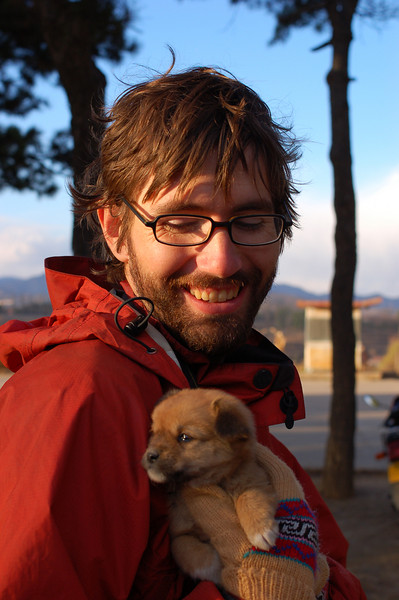 Pule Temple: Yann warms up a shivering puppy, note Yann has beautiful greasy hair.