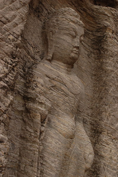 Layers of rock show through a Buddha