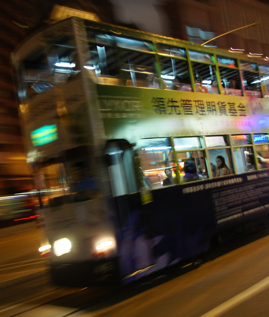 A tram driving by at night with motion blur - Hong Kong, China.  A travel photo from Hong Kong, China.
