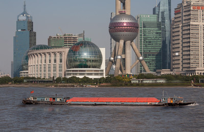 a busy Shanghai, China harbor with a barge