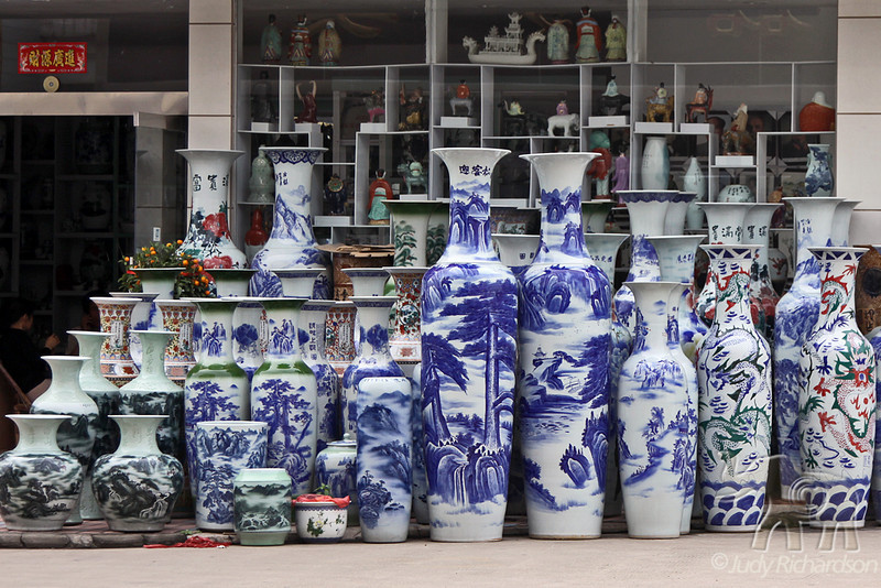 Various sizes of jugs in front of shop in town
