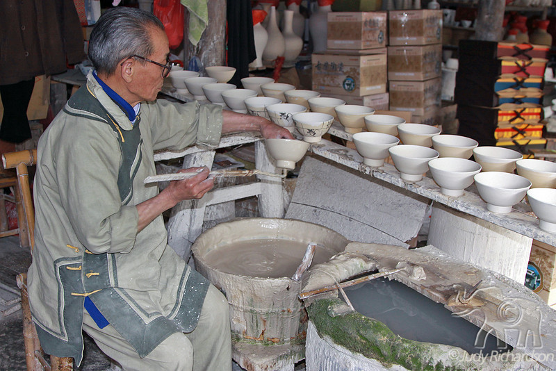 Worker glazing porcelain pot in workshop