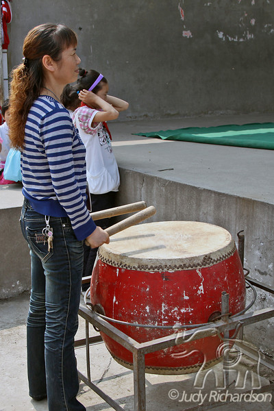 Teacher at Jingzhou Viking School performs on the drum while another student tries to block out sound