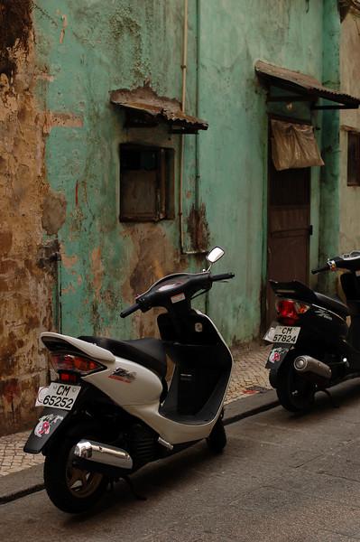 Mopeds parked along a narrow Macau street