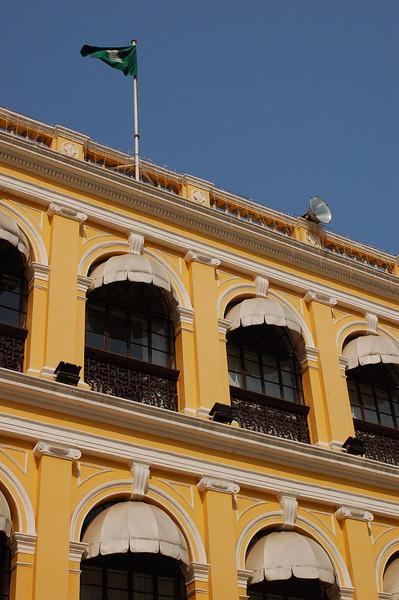 Green Macau flag flies over a municipal building