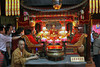 Mummified Buddha in Temple on Mt. Jiuhua with Monk watching tourists and incense pot on table