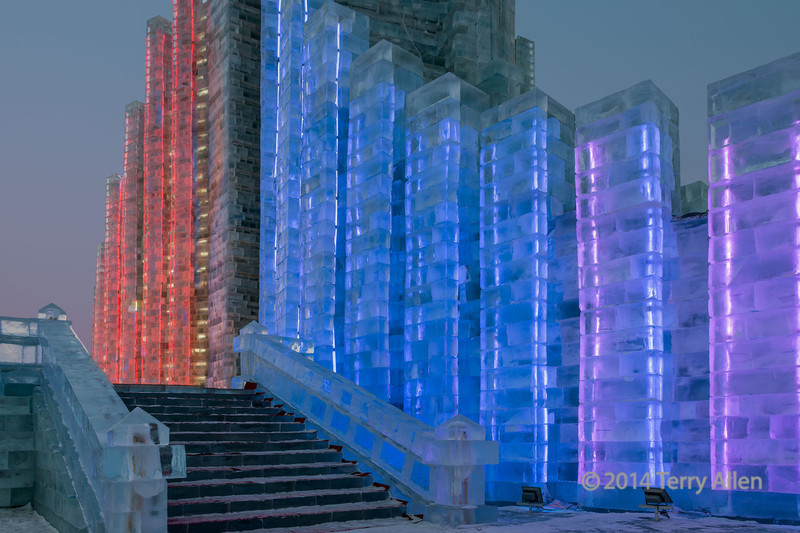 """Ice structure at the Harbin Ice Festival<br /> <br /> Looking forward to your alphabet day photos, but since I've posted all of mine, I am doing something different.  However I am saving an extra alphabet post for 'Z' day.<br /> <br /> The Harbin Snow and Ice Festival began in 1963, but was interrupted for several years during the Cultural Revolution.  It began again in 1985.  It is currently the largest in the world.<br />  <br /> This photo was taken after sunset when they started to turn on the lights embedded in the ice.  To get the best photos, it is ideal to go around sunset when the gates first open to avoid the late night crowds.  This way you can gradually find good photo spots for when the coloured lights come on, and also get some good light at sunset and some of the special cobalt light in the sky after the sun sets (and also moon rise).  The photos I've posted today set the scene and show the late day photos, and as this series continues, the sky will get darker and the colours more brilliant....and it gets colder.  It was well below freezing when we arrived and by the time we left it was -33C.  The challenge was to deal with the tripod shots in the cold and to get good exposures in the ever changing light.  At least the air pollution was only moderate.<br /> <br /> Other photos can be seen here: <a href=""""http://goo.gl/mfWhck"""">http://goo.gl/mfWhck</a><br /> <br /> 1/06/14  <a href=""""http://www.allenfotowild.com"""">http://www.allenfotowild.com</a>"""