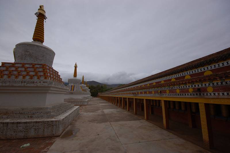 Row of chortens and prayer wheels at the Lower Wutun Monastery