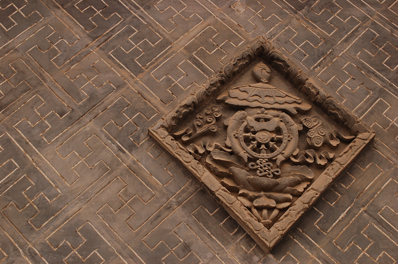 Buddhist symbols on the wall of the monastery.