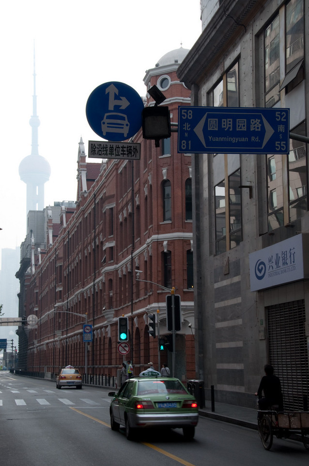 Shanghai's Oriental Pearl Tower seen in the background of a Shanghai street